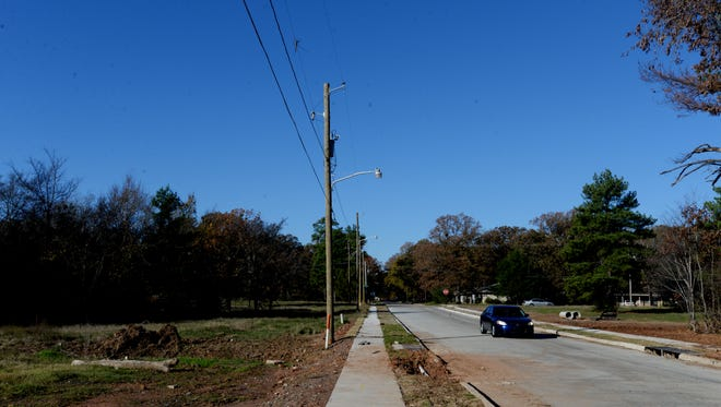 A car travels down the recently redone Hersey D. Wilson Dr. which already has visible cracks and drainage issues.