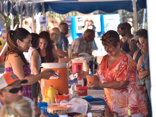 People gather underneath  a tent to get refreshments