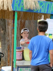 Four-year-old Rylee Allowishes Delaney is CEO and president of RAD Drinks, waits for a high five from a new customer.