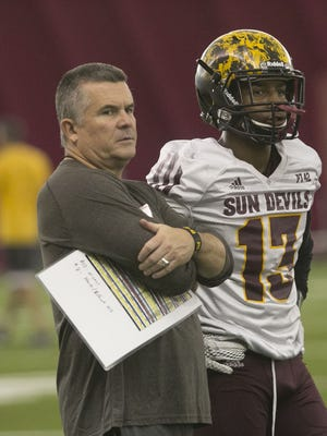 ASU head coach Todd Graham and Armand Perry (13) watch a drill during night practice at ASU's Dickey Dome in Tempe, AZ on August 10, 2015.