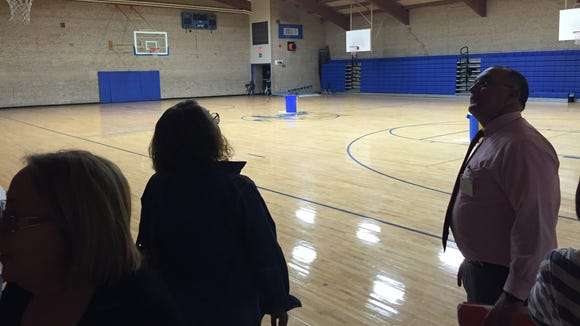 Ysleta Independent School District residents and administrators check out an Eastwood High School gym. The blue trash bins are collecting water from leaks in the roof, administrators said.