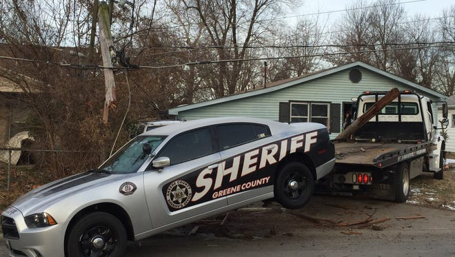 Police say a tow truck carrying a sheriff's deputy car crashed into a power pole Sunday morning in northwest Springfield.