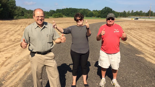 H.E.R.O. director Joanna Hardesty (center) gives Hamburg Township Supervisor Pat Hohl (left) a smack on his shoulder, and Bill Hahn, a township trustee who was a member of a special ad hoc committee that helped negotiate a plan for the Hamburg Family Fun Fest to continue using Manly W. Bennett Memorial Park, gives the thumbs up. Five acres of the park has been leveled, so amusement rides can be moved off of baseballs fields next summer.