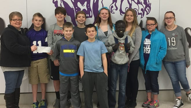 Sixth-grade students from Portland West present Penny Martin, director of Portland CARES. Front row, from left, Cooper Thurman, Camren Walden and Muk Buk. Second row, from left, Penny Martin, Nik Averitt, Colby Lane, Kaden Cole, Madison Young, Macy Vetetoe, Hannah Campbell and Kady Wiseman.