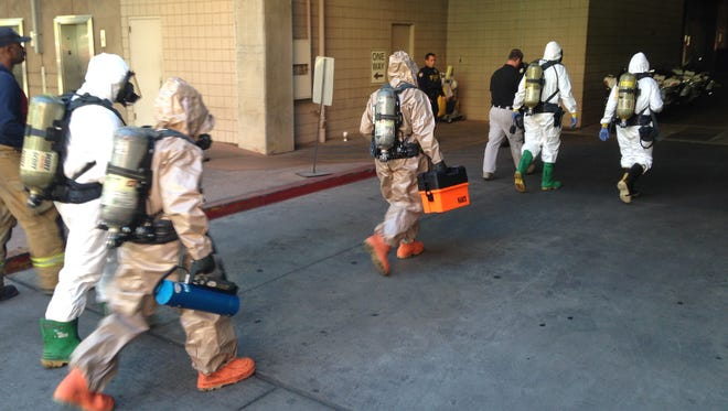 Crews enter the Phoenix building where a substance was found on Oct. 29, 2014.