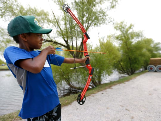 KamRay Rutledge, 8, pulls back on a bow and arrow during