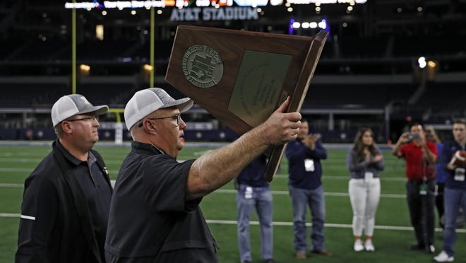 Head coach Michael Pittman holds up the runner-up trophy after Post lost in the Class 2A, Division I football state championship to Refugio on Dec. 18, 2019, at AT&T Stadium in Arlington.