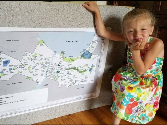 Lily Moore, 7, poses with a map Green Bay Parks, Recreation