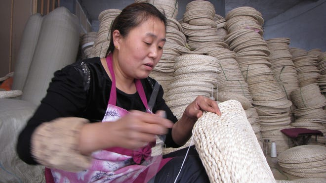 Wei Haiying, 39, stitches together a willow straw cushion for sale through Taobao, a huge, eBay-like online marketplace owned by Chinese Internet giant Alibaba.