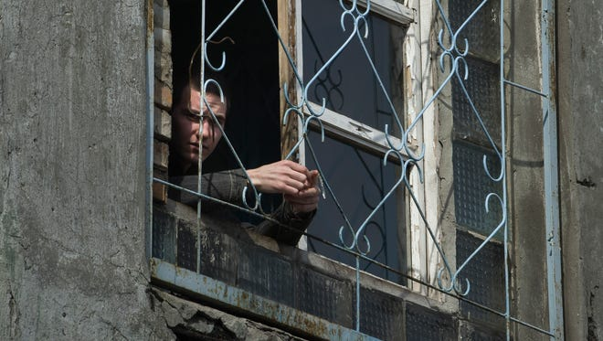 "In this photo taken on Thursday, March 26, 2015 a prisoner of Zhdanivskaya prison looks out of the window in the village of Zhdanivka, eastern Ukraine.Medical supplies have been in short supply, threatening the lives of nearly 400 prisoners who need treatment. The principal scourge: Tuberculosis. The disease spreads prodigiously in jails and develops into hard-to-treat forms unless properly addressed. ""TB is so common within the penitentiary system that many inmates don't see it as a deadly disease _ they see catching TB as a normal part of life in prison,"" Doctors Without Borders said in a recent situation report. ""Some even tell us they don't care if they die or not."" (AP Photo/Mstyslav Chernov)"