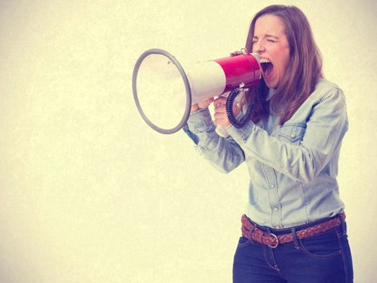 young woman shouting by megaphone