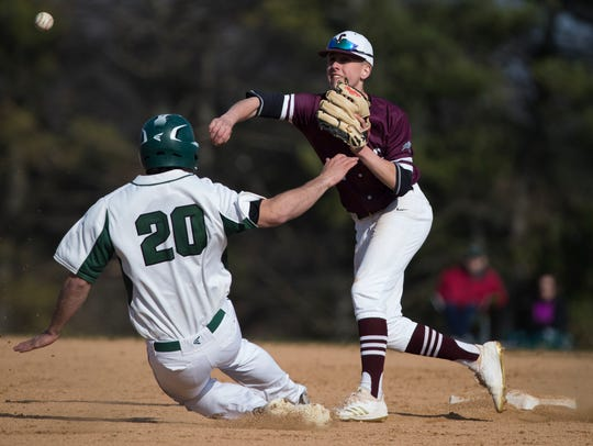 Caravel's Michael Summerfield (2) throws to first base as St. Mark's Dominic Catalano (20) slides into second base Tuesday at St. Mark's.