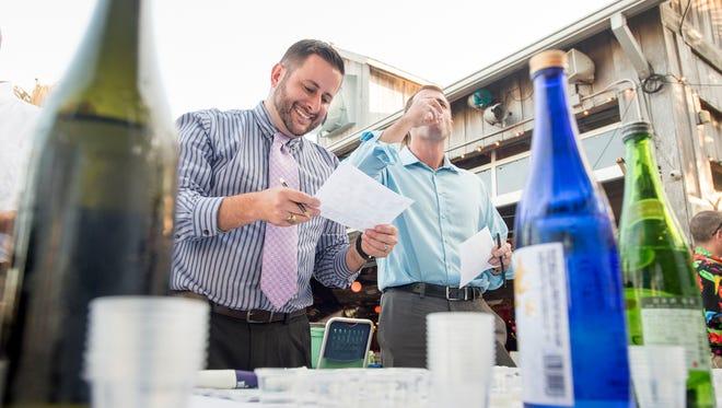 Drew Hardgrave, left, and Paul Green try samples of sake during the Premium Sake Tasting event at Flounders in Pensacola on Wednesday, November 29, 2017.