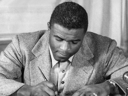 "NEW YORK, UNITED STATES:  (FILES)This undated file photo shows US baseball star Jackie Robinson as he signs a then-record contract to play for the Brooklyn Dodgers in New York. Robinson has been chosen to receive posthumously the Congressional Gold Medal, the highest award Congress can bestow on a US civilian, 02 March 2005, for his accomplishments on the baseball diamond, as well as ""his lifetime of breaking down barriers and his unending fight for justice,"" officials on Capitol Hill said in an earlier press release. US Senator John Kerry and US Representative Richard Neal, who co-sponsored legislation honoring Robinson, will be joined by the ballplayer's widow Rachel Robinson, US President George W. Bush and congressional leaders at the ceremony. Robinson broke baseball's ""color line"", becoming the first African American to play in the Major Leagues when he debuted with the Brooklyn Dodgers in 1947. Officials in Congress said however that he is also being honored for his contributions to the broader struggle for civil rights. AFP PHOTO  (Photo credit should read STR/AFP/Getty Images)"
