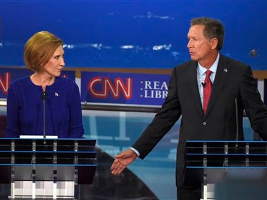 Republican presidential candidate, Ohio Gov. John Kasich, right, gestures as Carly Fiorina looks on during the CNN Republican presidential debate at the Ronald Reagan Presidential Library and Museum on Wednesday, Sept. 16, 2015, in Simi Valley, Calif.
