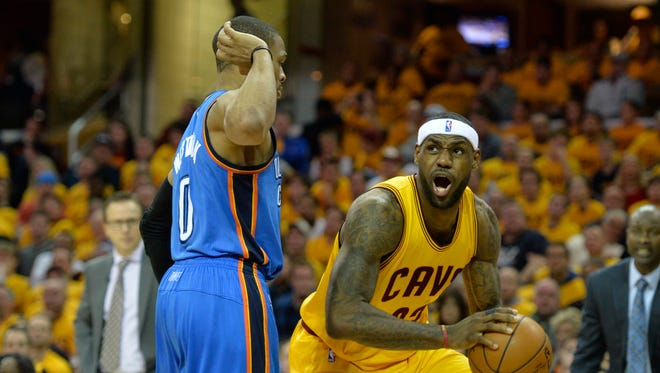 LeBron James (23) looks to shoot against Oklahoma City Thunder guard Russell Westbrook (0) in the fourth quarter at Quicken Loans Arena.