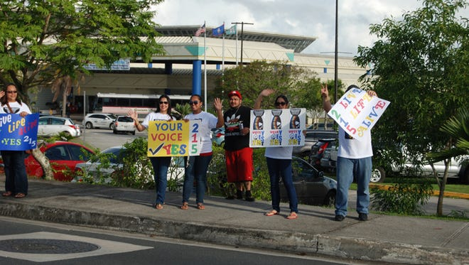 Members of the Live Life Alive nonprofit group wave to motorists at the Micronesia Mall intersection in Dededo in October 2014. The group held the wave to gather support to pass the medical marijuana measure on the November General Election ballot. Pacific Daily News file photo