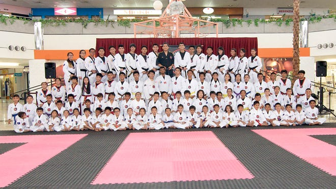 Competitors and officials join Noly Caluag (black gi), chief instructor of Guam Taekwondo Center, for a group photo during the opening ceremonies of the 2015 Taekwondo Sparring Tournament held recently at the Micronesia Mall.