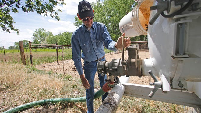 Don Moats, owner of D.J.'s Backhoe Service, works on a septic tank at a home in Fruitland in May. Most San Juan County septic-pumping companies have become certified through a state agency, but one has not.