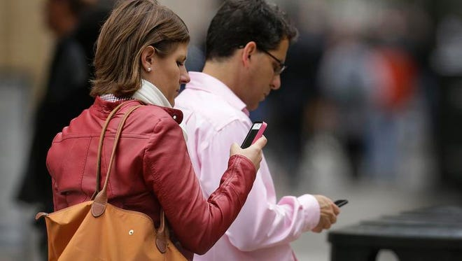 In this June 5, 2013, file photo, people use cellphones in downtown San Francisco. (AP Photo/Ben Margot, File)