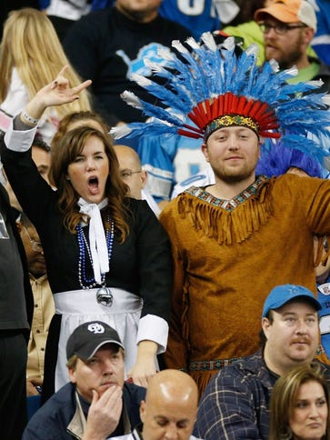 Fans cheer on Thanksgiving Day during the game between