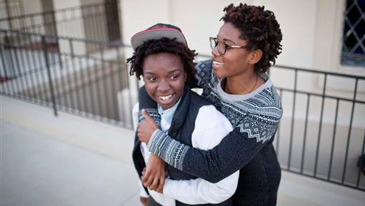Shanté Wolfe, left and Tori Sisson embrace near the Montgomery County Courthouse, Sunday, Jan. 25, 2015, in Montgomery, Ala., where they plan to stay overnight to be married Monday morning. A federal judge has stayed her order overturning Alabama's gay marriage ban for two weeks. (AP Photo/Brynn Anderson)