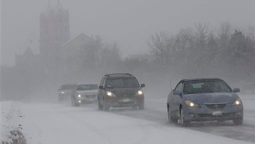 Traffic slowly moves down Waukegan Road on Sunday, Feb. 15, 2015, in Northbrook, Ill. Lake-effect snow that is expected to hang around Chicago until the middle of the afternoon is causing slippery conditions on some area roadways close to Lake Michigan, leading to multiple accidents like the one that fouled up traffic on the Kennedy Expressway Sunday morning and afternoon.