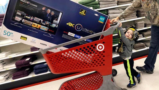 FILE - In this Friday, Nov. 25, 2016, file photo, Hunter Harvey helps his dad, C.J., wheel a big screen TV at Target, in Wilmington, Mass. The U.S. economy grew at a 3.5 percent annual rate in the July-September quarter, the fastest pace in two years and more than the government had previously estimated. But the growth spurt isn't expected to last. The gain in the gross domestic product, the economy's total output of goods and services, came from added strength in consumer spending, business investment and the government sector, the Commerce Department said Thursday, Dec. 22.