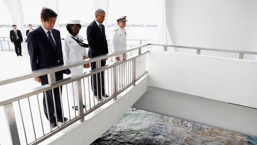 U.S. President Barack Obama and Japanese Prime Minister Shinzo Abe pause after tossing flower petals into the Wishing Well at the USS Arizona Memorial, part of the World War II Valor in the Pacific National Monument, in Joint Base Pearl Harbor-Hickam, Hawaii, adjacent to Honolulu, Hawaii, Tuesday, Dec. 27, 2016, as part of a ceremony to honor those killed in the Japanese attack on the naval harbor.