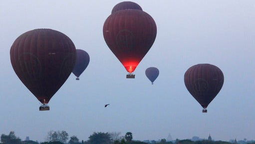 In this Tuesday, March 14, 2017 photo, hot air balloons are seen just after takeoff to fly over the ancient Myanmar city of Bagan. Balloon flights are a popular tourist activity in the city, which is home to the largest concentration of Buddhist temples, stupas and monuments in the world.