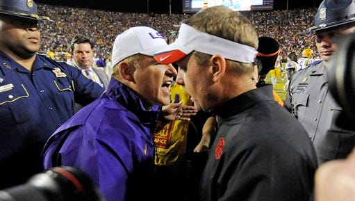 LSU head coach Les Miles, center left, and Ole Miss head coach Hugh Freeze, center right, talk after Saturday's game.