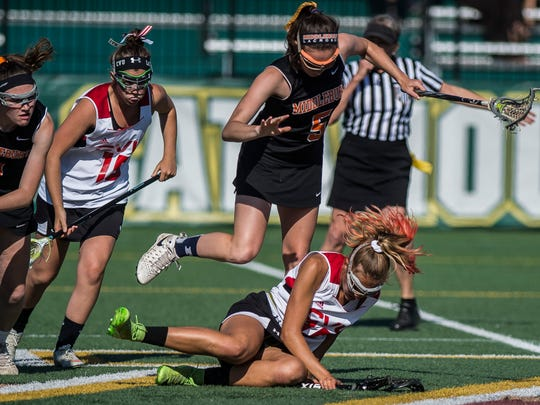Middlebury's Isabel Rosenberg (5) leaps over CVU's  Natalie Durieux (16) during their girls lacrosse championship battle at Virtue Field at UVM on Friday night, June 8, 2018.