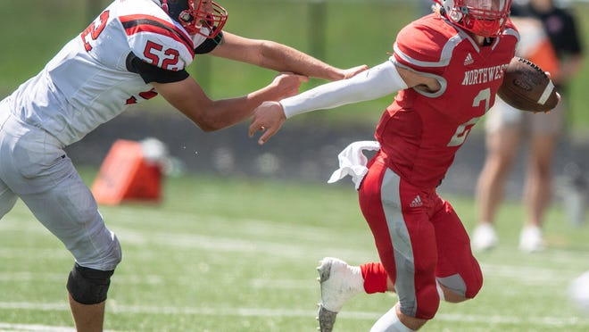 Northwest quarterback Jordan Mick eludes Orrville's Kyle Endsley during Saturday's resumption of their season opener. Mick threw for 392 yards and five touchdowns in the 42-7 Indians win.