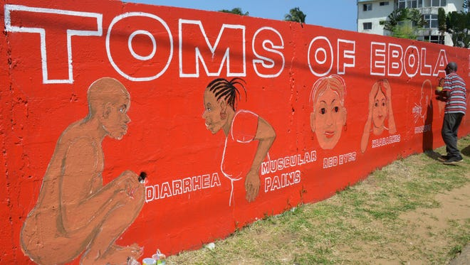 Liberian street artist Stephen Doe paints on Sept. 8, 2014, a mural to inform people about the symptoms of the deadly Ebola virus in Monrovia.