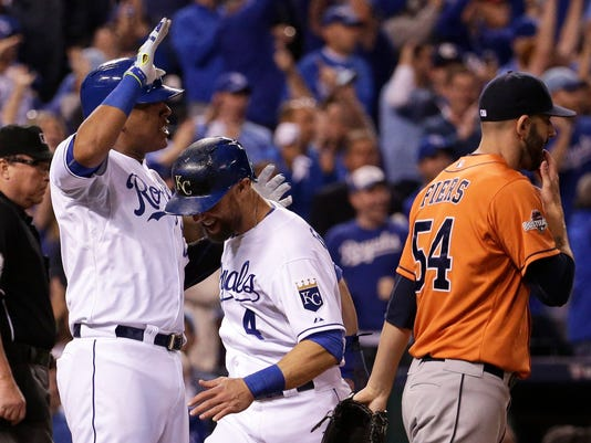 Kansas City Royals' Alex Gordon, center, and Salvador Perez, left, celebrate in front of Houston Astros pitcher Mike Fiers, right, after scoring on a double by teammate Alex Rios during the fifth inning of Game 5 in baseball's American League Division Series, Wednesday, Oct. 14, 2015, in Kansas City, Mo.  (AP Photo/Charlie Riedel)