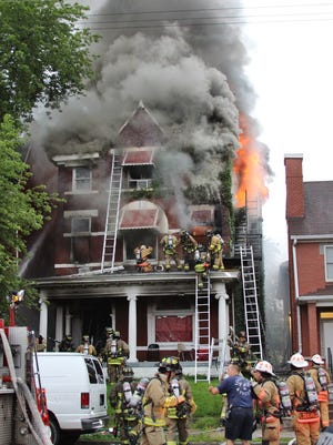 Firefighters hurry to rescue residents and a trapped firefighter minutes before the porch roof they're on collapses.