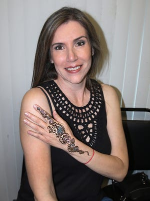 Ana Sahagun shows off her henna art by Tejal Patel.