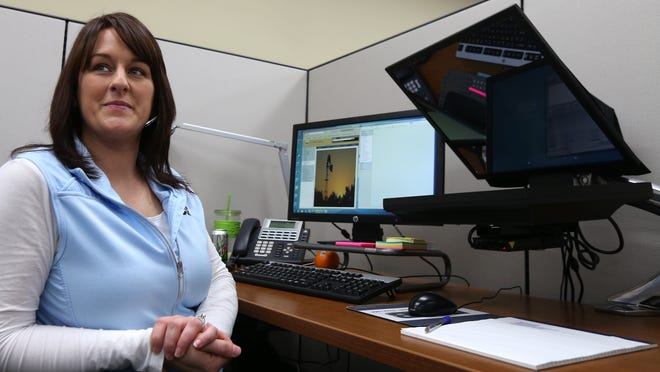 Amanda Graves, an interactive teller at PCSB Bank in Clarinda, Iowa, helps customers via an online connection from a cubicle.