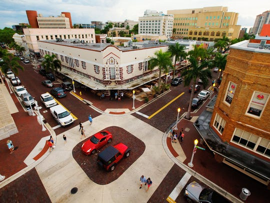 People and traffic flow through downtown Fort Myers