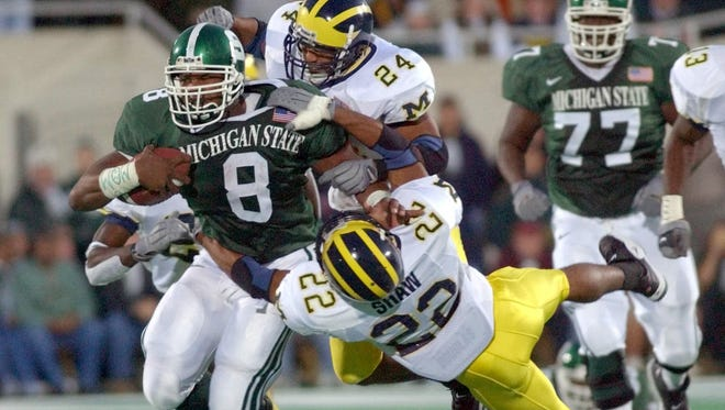 Michigan State running back T.J. Duckett dashes down the field dragging Michigan players with him in the Spartans' controversial victory in 2001.