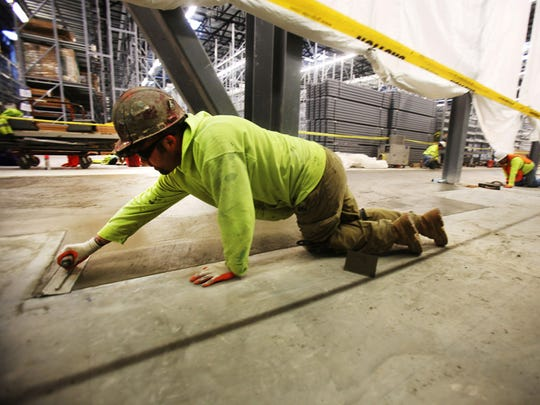 David Hankins of Howell is finishing the concrete by  getting all of the edges flat in the newly expanded portion of Ikea in Canton.