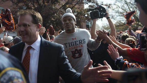Auburn head coach Gus Malzahn leads Cam Newton, former