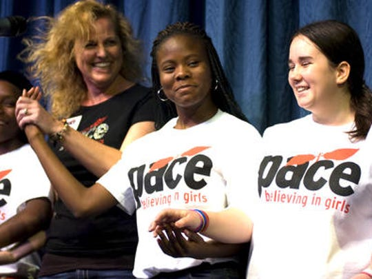 Andrea Prather, Board of Directors, PACE Center for Girl's students Ebonnee, center, and Alyssa, sing to a crowd of supporters in 2014. This year's Grande Dames Tea is Tuesday.