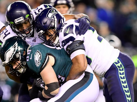 PHILADELPHIA, PENNSYLVANIA - JANUARY 05: Dallas Goedert #88 of the Philadelphia Eagles is tackled by K.J. Wright #50 and Bobby Wagner #54 of the Seattle Seahawks during the NFC Wild Card Playoff game at Lincoln Financial Field on January 05, 2020 in Philadelphia, Pennsylvania. (Photo by Steven Ryan/Getty Images)