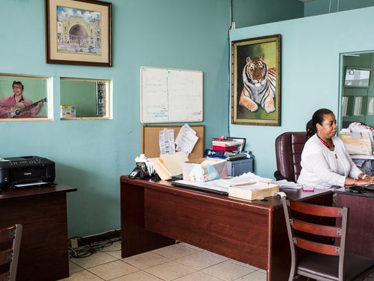 Office manager Patrice Gray works at her desk June