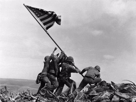 Marines raise the American flag atop Mount Suribachi during the Battle of Iwo Jima on Feb. 23, 1945. This flag replaced a smaller flag that had been planted there after the mountain was captured by Marines. Al Wilson of Alexandria, who was only about 500 feet away when the flag was planted both times, said that contrary to popular belief, the planting of the flag for a second time was not staged for photo purposes. This photo by AP photographer Joe Rosenthal became one of the most iconic images of World War II.