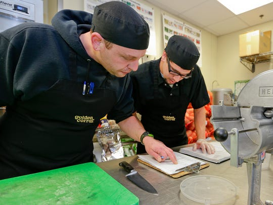 Golden Corral assistant manager Warren Ellis, left, and Jacob Canning, a new crew member, go over a list before the restaurant opens.