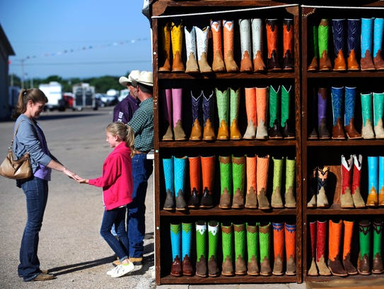 Callie Carter plays a game with her daughter 9-year-old Lacie as her husband Mike talks with a friend. The Fredericksburg family was waiting for their food next to a boot vendor during the 2017 Western Heritage Classic.