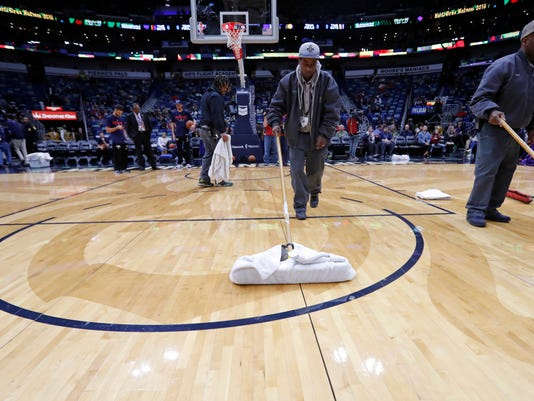 Workers mop the court during a delay for the start of an NBA basketball game against the Indiana Pacers in New Orleans, Wednesday, Feb. 7, 2018. The game was under a delay due to moisture falling from the rafters onto the court. (AP Photo/Gerald Herbert)