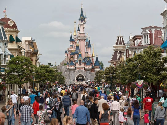 Visitors walk toward the Sleeping Beauty's Castle at
